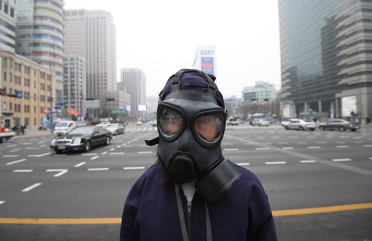 3月6日,一名示威者戴上面罩,在光化门广场表达诉求,要求首尔政府处理连日来的空气污染问题。(Jung Yeon-Je/法新社)